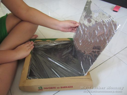 Cover the opening with clear plastic wrap. (Pizza box solar oven)