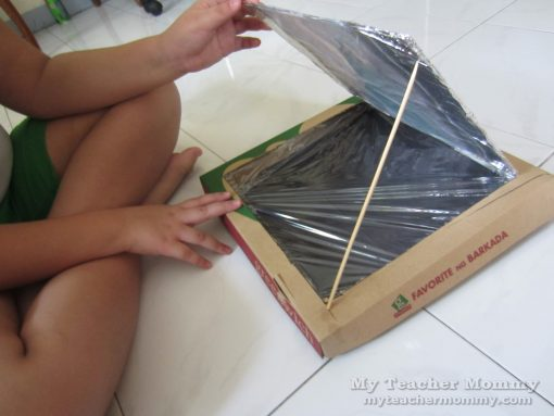 Use a barbecue skewer to hold up the flap at an angle. (Pizza box solar oven)